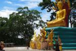 """Žena klečí před obří sochou Budhy, který je chráněn mýtickým hadem """"naga"""" se sedmi hlavami."""