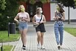 Dívky s rouškami na obličejích procházejí 20. července 2020 po ulici ve Vlčnově na Uherskohradišťsku