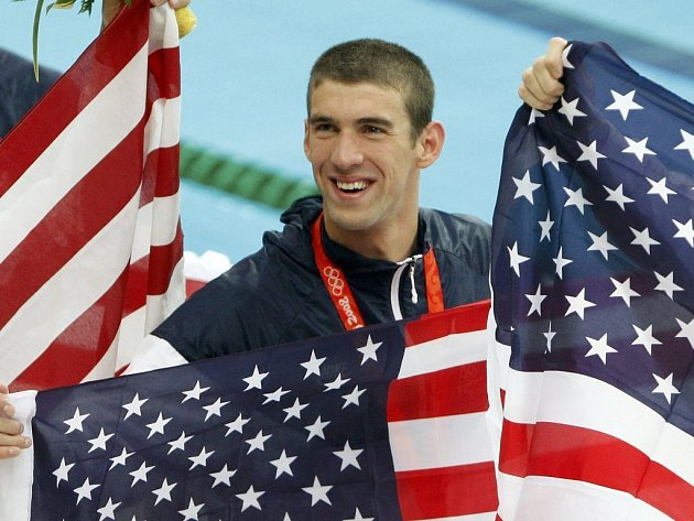 Plavec Michael Phelps mezi americkými vlajkami.