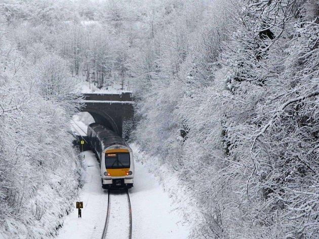 Vlak jede po silném sněžení v Princes Risborough v jižní Anglii.