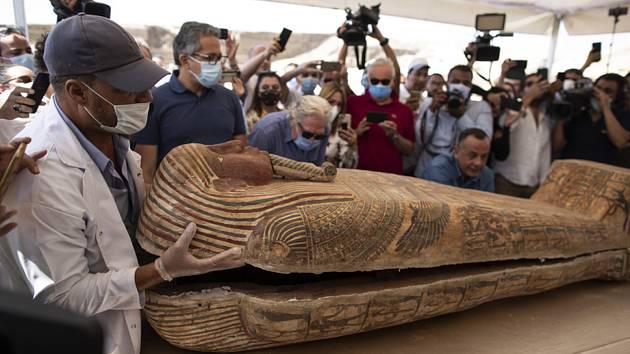 Archeolog otevírá za přítomnosti novinářů a úředníků jeden ze sarkofágů z archeologického naleziště v Sakkáře.