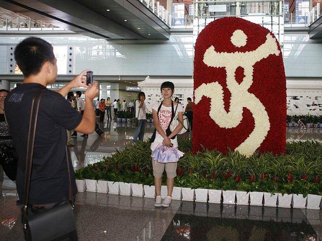 Číňané cestující na Tchaj-wan se fotografují před olympijským znakem letošních her na mezinárodním letišti v Pekingu. Díky politickému tání ledů mezi Pekingem a Tchaj-pejí jich nyní na vzpurný ostrov může létat každý den až 3000.