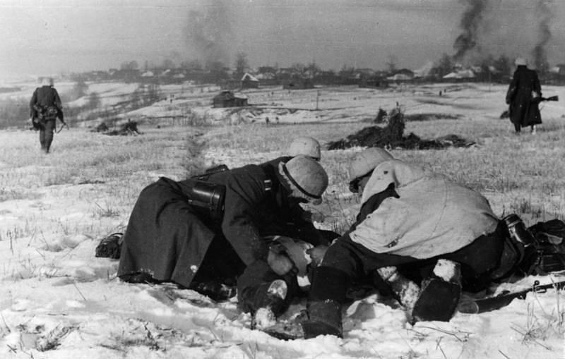 Němečtí vojáci se snaží odvléci zraněného spolubojovníka, listopad nebo prosinec 1941, bitevní pole před Moskvou