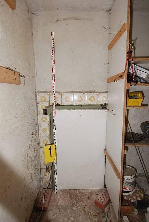 Vstup do tajného sklepního vězení zakrývají nevelké železobetonové dveře ukryté za policemi. Otvírají se elektronicky, na číselný kód.