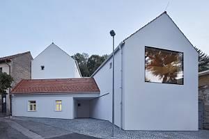 Štítové stěně dominuje velké fixní okno v líci fasády, za kterým se nachází malá pracovna.