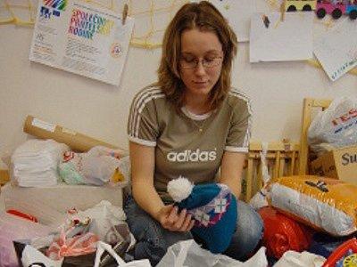 Marcela Helena Marková z Krušnohorského centra pro rodinu a sociální péči v Mostě třídí zimní oblečení darované veřejností.