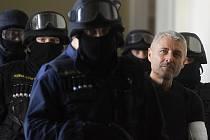 Policejní těžkooděnci doprovázejí hoteliéra Bohumíra Ďurička k soudnímu líčení, které pokračovalo u Městského soudu v Praze.