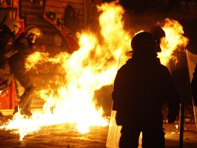 Policisté uskakují po dopadu Molotovova koktejlu v Aténách.