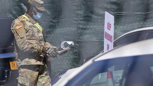 Příslušník národní gardy v roušce vypomáhá s testováním na koronavirus na odběrovém místě v newyorském Brooklynu.