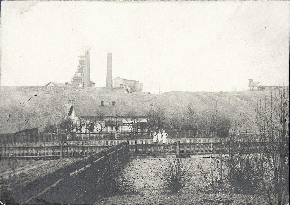 Záběr na jámu Františka, v popředí dům s polem a děvčaty. Dne 4. června 1894 zahynulo v tomto dole 235 horníků