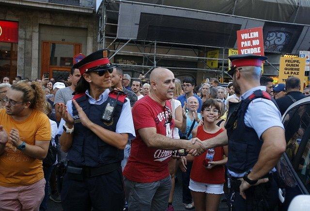 Lidé se v Madridu zdraví s policisty.