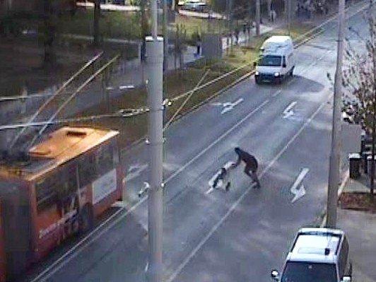 Městský kamerový systém zachytil opilého muže, jak s kočárkem přechází rušnou silnici za plného provozu, načež se mu kočárek vysmeknul z ruky.