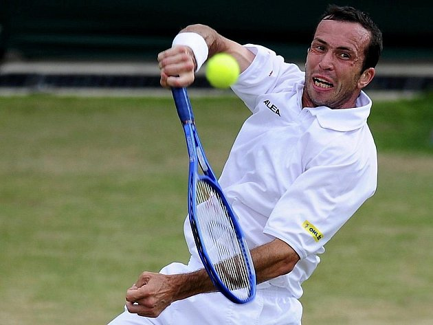 Radek Štěpánek odvrací míček v zápase s Lleytonem Hewittem ve 4. kole Wimbledonu.