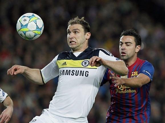Barcelonský Xavi atakuje Ivanoviče z Chelsea.