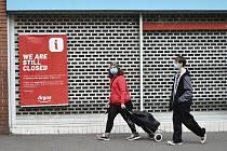 Lidé v rouškách procházejí kolem uzavřené prodejny v britském Leicesteru