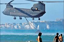 Vrtulník italského námořnictva nabírá vodu na hašení jednoho z mnoha požárů přímo na pláži v letovisku Gargano.