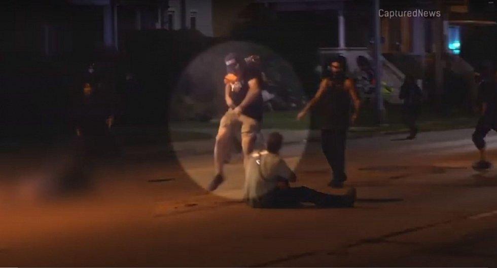 Okamžik střelby. Obviněný sedmnáctiletý Kyle Rittenhouse je na zemi, střelbou se v tu chvíli brání útoku