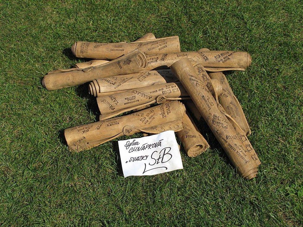"""Keramický výrobek Sylvy Chňapkové znázorňující """"StB svazky"""", prezentovaný na hrnčířských trzích v Berouně v roce 2011"""