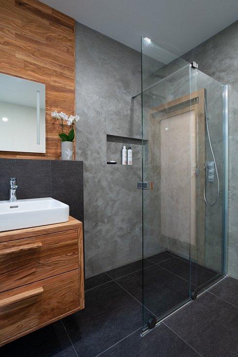 V nice nad vanou i na nábytku v koupelně je použito olivové dřevo.