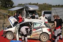 Mechanici pracují na Peugeotu Jana Kopeckého při testech na Portugalskou rallye.