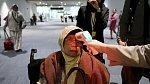 Zdravotník měří teplotu ženě na mezinárodním letišti v indonéském Tanggerangu na snímku z 22. ledna 2020