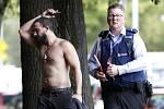 Policista doprovází jednoho z mužů, který uprchl před střelbou v mešitě v novozélandském Christchurch.