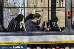 Lidé s rouškami na obličejích jako ochranou proti koronaviru 18. března 2020 cestují poloprázdnou tramvají na Náměstí Míru v Praze
