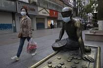 Žena v roušce prochází kolem bronzové sochy, která má na sobě také roušku, v čínském Wu-chanu (na snímku z 13. dubna 2020)