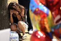 Žena truchlí u pomníku za oběti střelby v americkém Denveru.