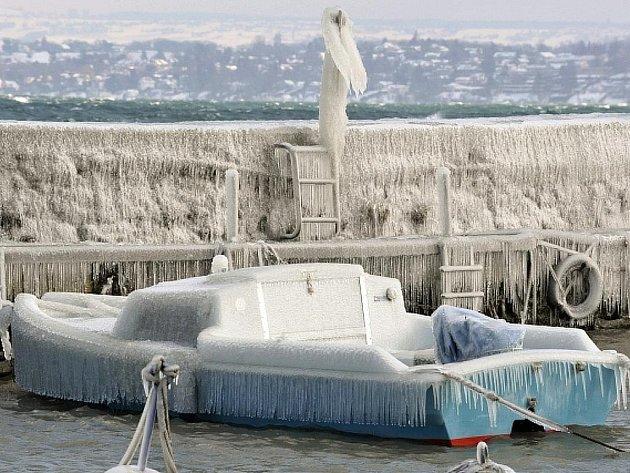 Loď celá pokrytá ledem na jezeře v Ženevě.