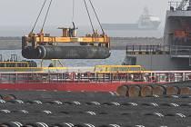 Jeřáb nakládá na loď potrubí pro plynovod Nord Stream 2 v baltském přístavu Mukran.