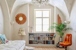 Tmavý středověký byt s bílou výmalbou a hnědým nábytkem oživil dekor oškrabaného stropu, francouzský křišťálový lustr a zařízení ve světlých barvách s barevnými akcenty. Podlaha byla zbroušena a opatřena nátěrem s bílým pigmentem.