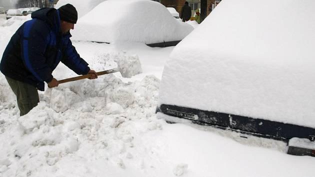 Muž uklízí sníh v Rumunsku