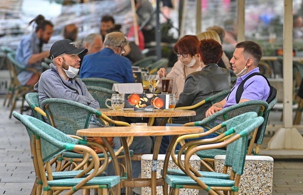 Lidé sedí 11. května 2020 na zahrádce jedné z restaurací v centru Brna. Po přestávce vynucené šířením nového typu koronaviru mohly restaurace a kavárny otevřít své předzahrádky, za další dva týdny otevřou i vnitřní prostory.