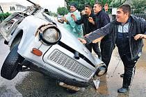VODA PŘEVRACELA TRABANTY. Muži staví na kola trabanta, kterého převrátil a odnesl proud rozvodněné řeky ve městě Tzaru. Po vlně čtyřicetistupňových veder zasáhly Bulharsko povodně.