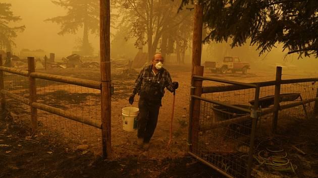 Muž nese kbelík s vodou na uhasení stromu, který stále doutná poté, co přes jeho pozemek přešel lesní požár