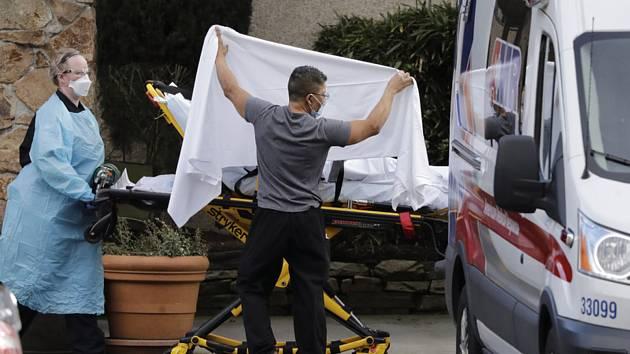 Zdravotníci nakládají do sanitky pacienta s podezřením na nákazu koronavirem u zařízení dlouhodobé péče v americkém městě Kirkland