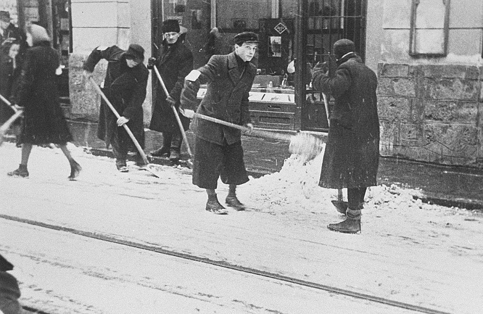 Židovští obyvatelé krakovského ghetta jsou nuceni odklízet sníh z ulice. Mnoho obyvatel ghetta podlehlo zimě a hladu