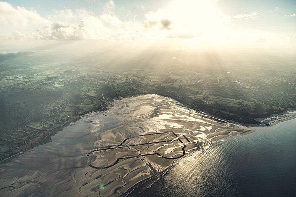 Na pláži Red Wharf Bay vAnglesey vytvořilo šestLand Roverů kilometrovou kresbu vpísku.