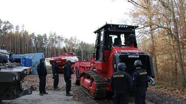 Policistům opět v areálu muničních skladů ve Vrběticích pomáhají armádní pyrotechnici. Při ohledání místa vybuchlého skladu číslo 16 pyrotechnici využívají i nový stroj, speciální pásový nakladač Caterpillar 973D.