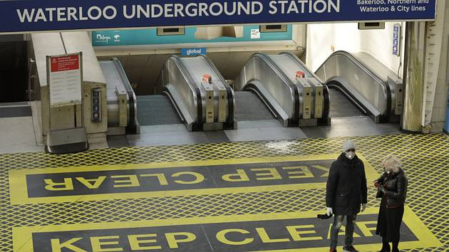 Lidé s rouškami ve stanici v londýnského metra 24. března 2020