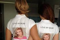 """Dívky stojí zády k fotoaparátu a ukazují bílá trička s natištěnou fotografií Nagyové a s nápisem """"Miluji svoji mámu""""."""
