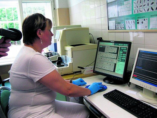 Laborantka srovnává prvky vyskytující se ve vzorku moči.