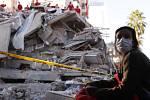 Obyvatelka Izmiru sleduje 31. října 2020 turecké záchranáře při prohledávání trosek jedné z budov po zemětřesení, které město postihlo o den dříve