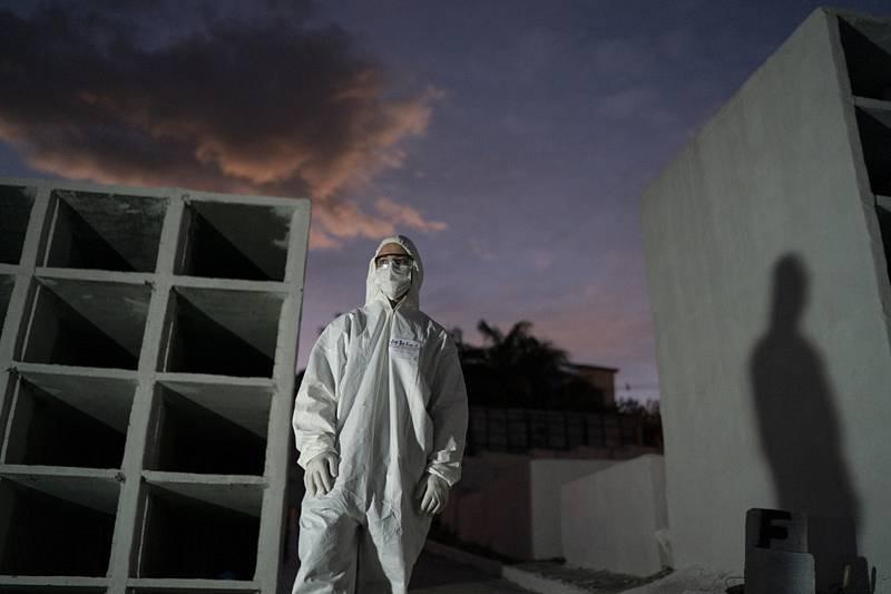 Pracovník hřbitova v ochranném obleku před pohřbem oběti koronaviru v brazilském městě Nova Iguacu