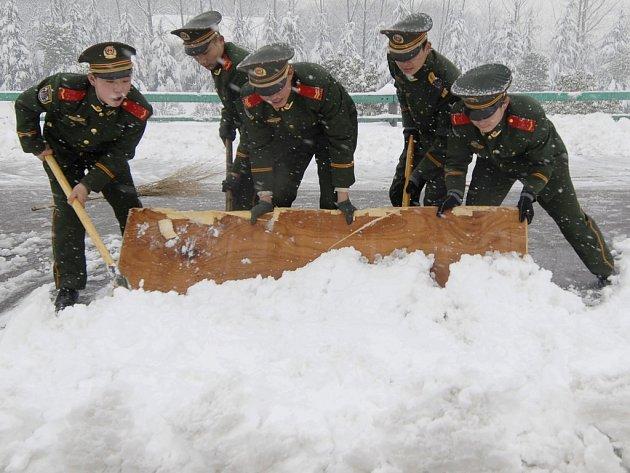 Čínští policisté se snaží odklidit sníh z dálnice.