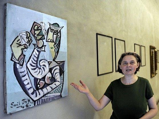 Ředitelka galerie v Lounech Alica Štefančíková ukazuje jeden z uloupených obrazů Žena s kartami, 1946, olej na plátně, 67 x 51.