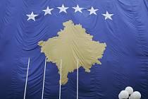 Vlajka s šesti hvězdami a obrysem Kosova.