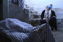 Oběť tureckého útoku v Sýrii - Příbuzná oplakává ženu zabitou při tureckém útoku na syrské město Kámišlí (tělo obětí v popředí) na snímku z 10. října 2019.