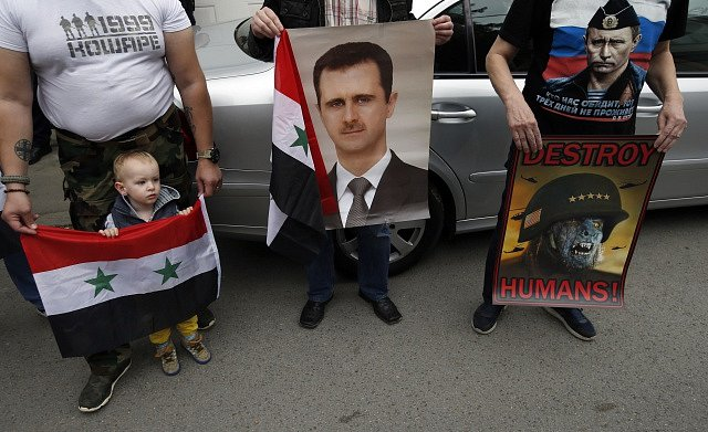 Protesty proti americkému útoku na Sýrii. Demonstranti přišli se syrskými vlajkami a fotografií prezidenta Asada.